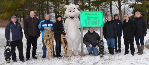 Shown at the entrance to the MacNaughton-Morrison Section of the South Huron Trail, are some of the organizers and supporters, along with Exeter's White Squirrel, getting ready for Family Day WinterFest South Huron. (left to right): Tim Cumming, Ausable Bayfield Conservation; Tim Sweet, Exeter Curling Club; Lorne Rideout, Friends of the South Huron Trail; Judy McLeod, Exeter Lioness Club; George Finch, organizer; Jean Jacobe, Trivitt Memorial Anglican Church; Jo-Anne Fields, Manager of Community Services, Municipality of South Huron; Darcey Cook, Municipality of South Huron Recreation Department Program and Events Assistant; and Maggie Miller, Big Brothers and Big Sisters of South Huron.