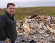 Paul Sherban, who is site supervisor of the Mid-Huron Landfill Site, stands by the piles of shingles and wood in this 2011 file photo.